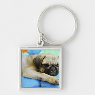 Pug laying on pillows keychain