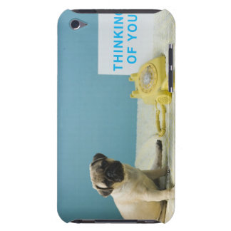Pug puppy sitting on bed next to and iPod Case-Mate case