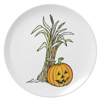 pumpkin next to corn shock graphic plate