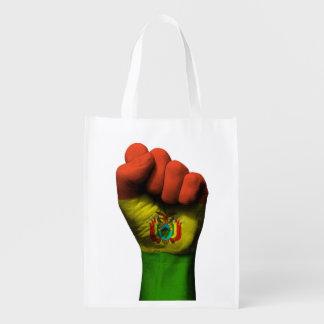 Puño apretado aumentado con la bandera boliviana bolsa para la compra