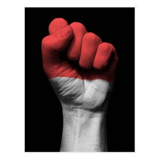 Puño apretado aumentado con la bandera indonesia postal