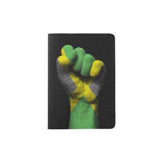 Puño apretado aumentado con la bandera jamaicana porta pasaporte