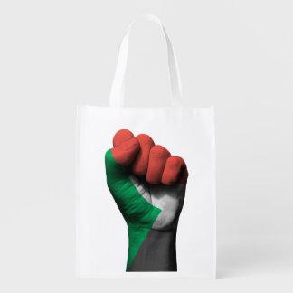 Puño apretado aumentado con la bandera sudanesa bolsa para la compra