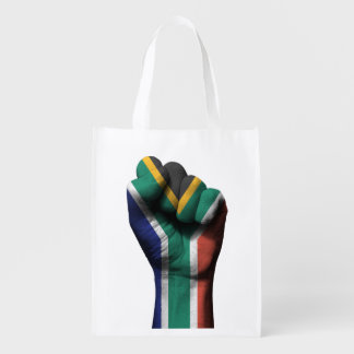 Puño apretado aumentado con la bandera surafricana bolsas de la compra