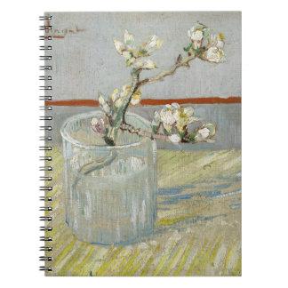 Puntilla de la almendra floreciente en un vidrio libro de apuntes con espiral