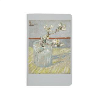 Puntilla de la almendra floreciente en un vidrio cuaderno