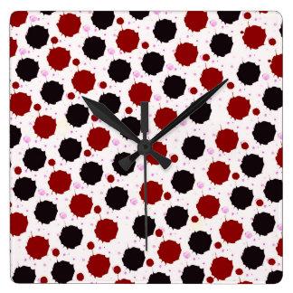 Puntos del chapoteo del rojo y del negro reloj cuadrado