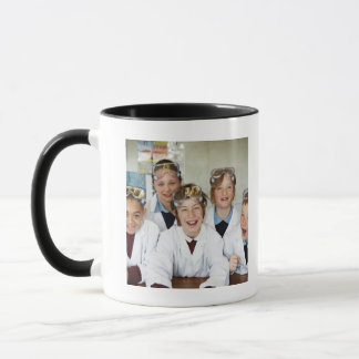 Pupils (9-12) in science class, smiling, mug