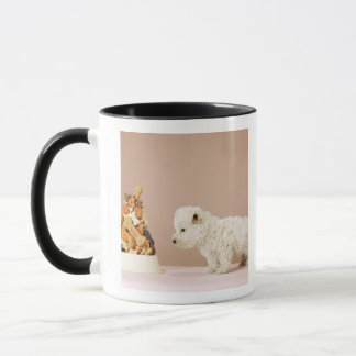 Puppy looking at pile of biscuits in dog bowl mug