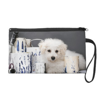 Puppy sitting amongst paint tins wristlet purse