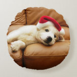 Puppy wears a christmas hat and lying on sofa round pillow