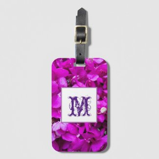 Purple orchid background with capital letter luggage tag