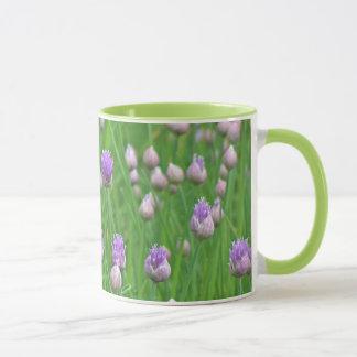PURPLE THISTLE-LIKE FLOWERS IN A FIELD OF GREEN MUG