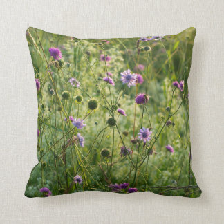 Purple wild flowers in a green meadow throw pillow