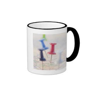 Pushpins in a map coffee mugs