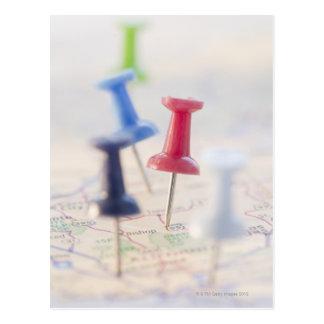 Pushpins in a map postcard