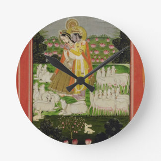 Radha and Krishna embrace in an idealised landscap Round Wall Clocks