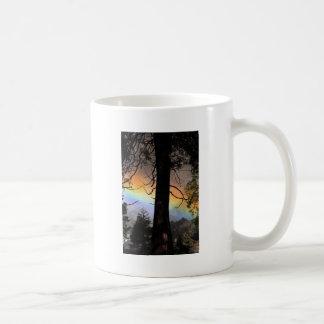 Rainbow bright behind a tree. coffee mugs