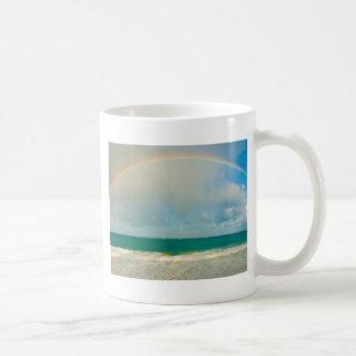 Rainbow over ocean coffee mugs