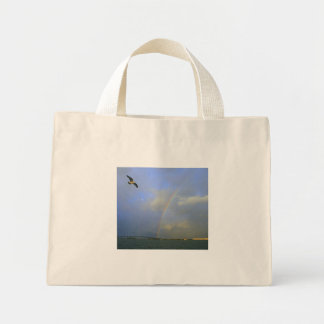 Rainbow over river bridge with seagull photo canvas bags