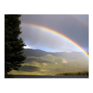 Rainbow over water against mountains postcard