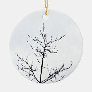 Rama de árbol seca contra el cielo nublado adorno navideño redondo de cerámica