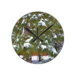Rama del pino debajo de la nieve reloj de pared