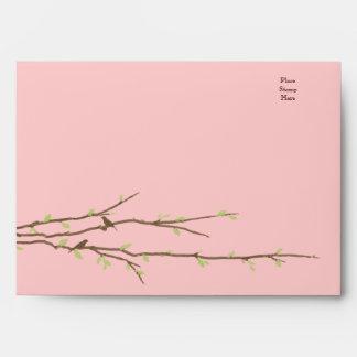 Ramas de florecimiento con los pájaros rosados y e sobres