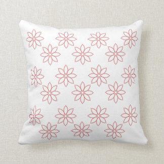 Ramilletes rojos Doted en la almohada blanca