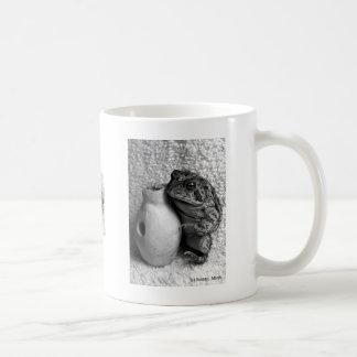 Rana del sapo que sostiene la fotografía de la per taza