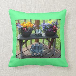 Ranas y banco de la almohada con las flores