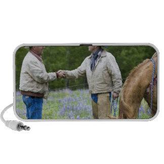Rancheros que sacuden las manos a través de encerr laptop altavoces