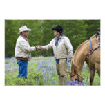 Ranchers shaking hands across the fencing in photo print