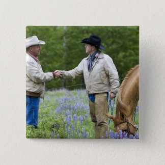 Ranchers shaking hands across the fencing in pinback button