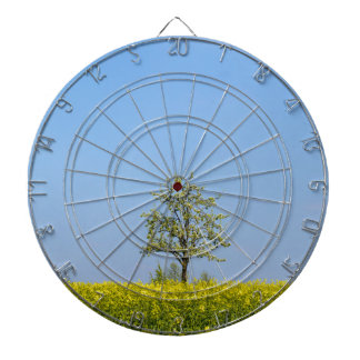 Rapeseed field with apple tree and blue sky dartboard