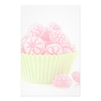 Raspberry tasty candy sweets in green cup cake stationery