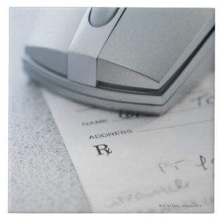 Ratón del ordenador en la prescripción escrita teja