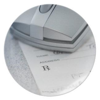 Ratón del ordenador en la prescripción escrita plato