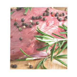 Raw beef with herbs and spices at the kitchen notepad