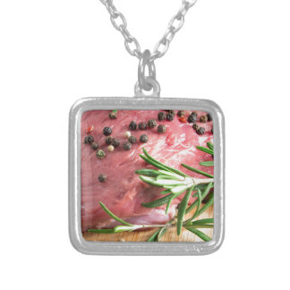 Raw beef with herbs and spices at the kitchen silver plated necklace