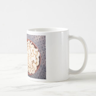 Raw cashew nuts in a brown bowl on fabric coffee mug