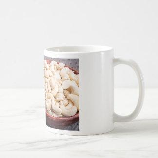 Raw cashew nuts in brown bowl on fabric background coffee mug