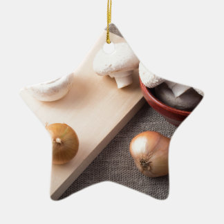 Raw champignon mushrooms and onions on the table ceramic ornament