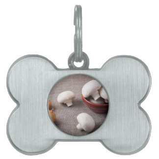 Raw champignon mushrooms and onions on the table pet ID tag