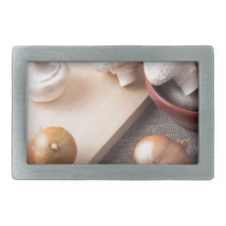 Raw champignon mushrooms and onions on the table rectangular belt buckle