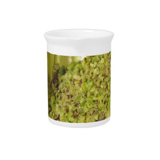 Raw chopped pistachios in a plastic food pan beverage pitcher