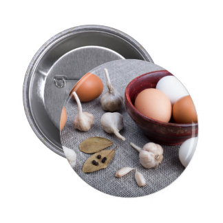Raw eggs and garlic and spices on the kitchen pinback button