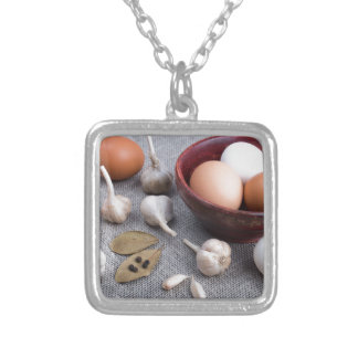 Raw eggs and garlic and spices on the kitchen silver plated necklace