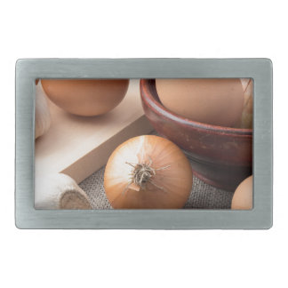Raw eggs, onions and garlic on a background belt buckle