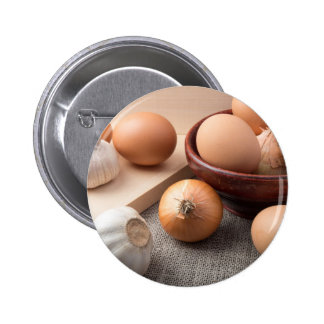 Raw eggs, onions and garlic on a background button